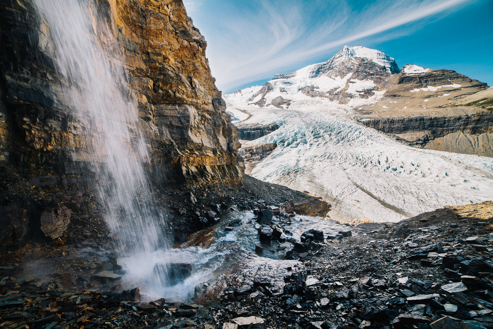 hidden waterfall with mount robson glacier in the distance